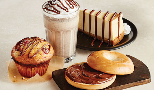 coffee culture - bagel with chocolate spread, chocolate milkshake, cheese cake and muffin with chocolate drizzle
