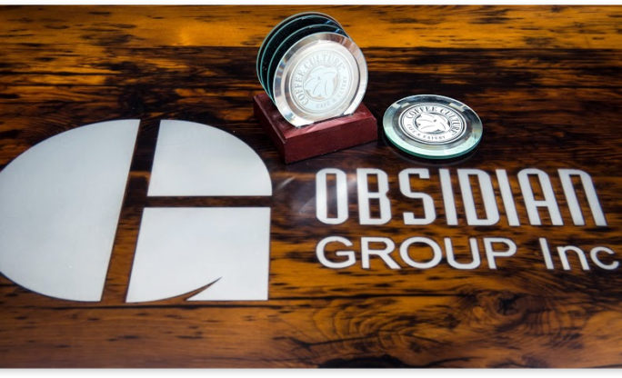 obsidan group logo on wood background and coffee culture coasters