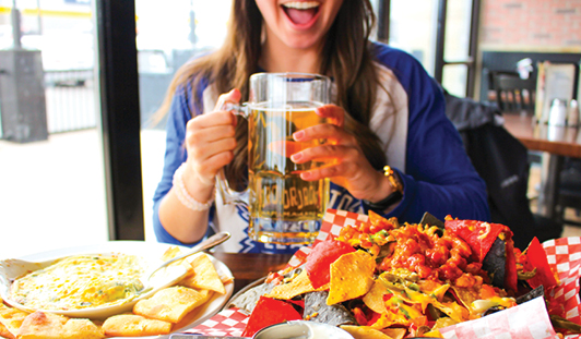 girl drinking beer from a large schooner, with nachos and spinach dip, at chucks road house